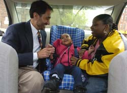 Randall S. Jotte, M.D., associate professor of medicine, explains to Tondra Holman how to properly restrain her 1-year-old daughter, Kenisha, in a car seat provided by the Safe and Secure program at the Grace Hill Soulard Neighborhood Health Center.