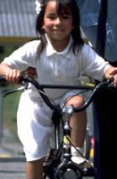While this adorable little girl seems to be having a good time, she is also violating safe bicycling Rule # 1: always wear a helmet.