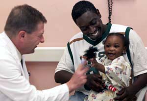 David M. Jaffe, M.D. (left), plays with finger puppets to help put 1-year-old Amar Robinson at ease before she's examined. Her father, Andrew, brought his daughter into the ED for treatment of an ear infection last week. Robert Kennedy, M.D., associate professor of pediatrics, says Jaffe has an amazing ability to connect with children.