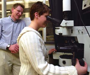 Lars Angenent guides graduate student Rebecca Hoffman as she examines bacteria from air digesters under a high-powered epifluorescence microscope.