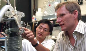 Jason He (left) and Lars Angenent inspect their microbial fuel cell. The researchers want to scale up the device for industrial use.