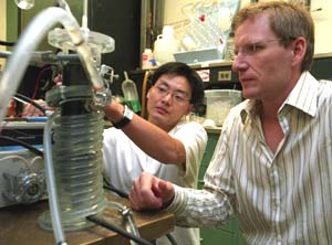 Lars Angenent (right) and doctoral student Jason He examine the upflow microbial fuel cell, which uses bacteria to treat wastewater and create electricity. Eventually, the device could handle the 2 million gallons of wastewater needed to create power for 900 homes.