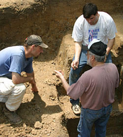 T.R. Kidder (seated in white shirt), professor of anthropology in Arts & Sciences, discusses the stratigraphy of Poverty Point's largest mound, Mound A, with Anthony Ortmann (left), graduate student at Tulane University, and Jon Gibson, professor of anthropology at the University of Louisiana at Lafayette.