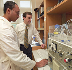 Donald Elbert (right) working with his graduate student Evan Scott at the optical waveguide light spectroscope to observe proteins sticking to a polymer surface in their Whitaker Building laboratory.