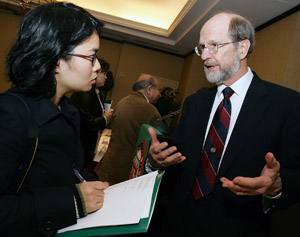 John F. McDonnell, vice chairman of the Board of Trustees, discusses the formation of the McDonnell International Scholars Academy with reporter I Ching Ng of *Ming Pao Monthly*, based in Albany, N.Y.