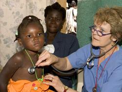 Patricia Wolff, M.D., examines a young patient in her pediatric clinic in Cap Haitien, Haiti, while the girl's mother looks on. Wolff's clinic is often the only medical care available to children in Cap Haitien.