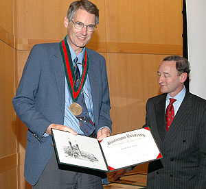 Jonathan S. Turner, Ph.D., (left) receives the Barbara J. and Jerome R. Cox Jr. Professor of Computer Science medal and a certificate from Chancellor Mark S. Wrighton. The professorship was established to advance the relationship between theory and practice in the design of digital systems.