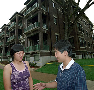 Ziyan Zhang and Yanjiao Xie, both of Peking University, visit outside the two furnished apartment buildings at Pershing Avenue and Skinker Boulevard where most of the McDonnell Academy scholars reside.