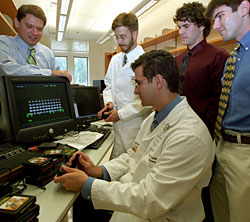 The doctors with joysticks (Eric Leuthardt, seated, and Mathew Smyth, standing) engage in a game of Space Invaders.