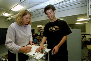 Shirley Dyke (left) and Pengcheng Wang  adjust wireless sensors onto a model laboratory building in Dyke's laboratory.  Dyke is the first person  to test wireles sensors in  simulated structural control experiments  She envisions  a wireless future for structural control technology.