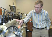 Lars Angenent, Ph.D., assistant professor of energy, environmental and chemical engineering, points to the mixed medium of thousands of organisms that help turn treated wastewater into electricity in this microbial fuel cell.