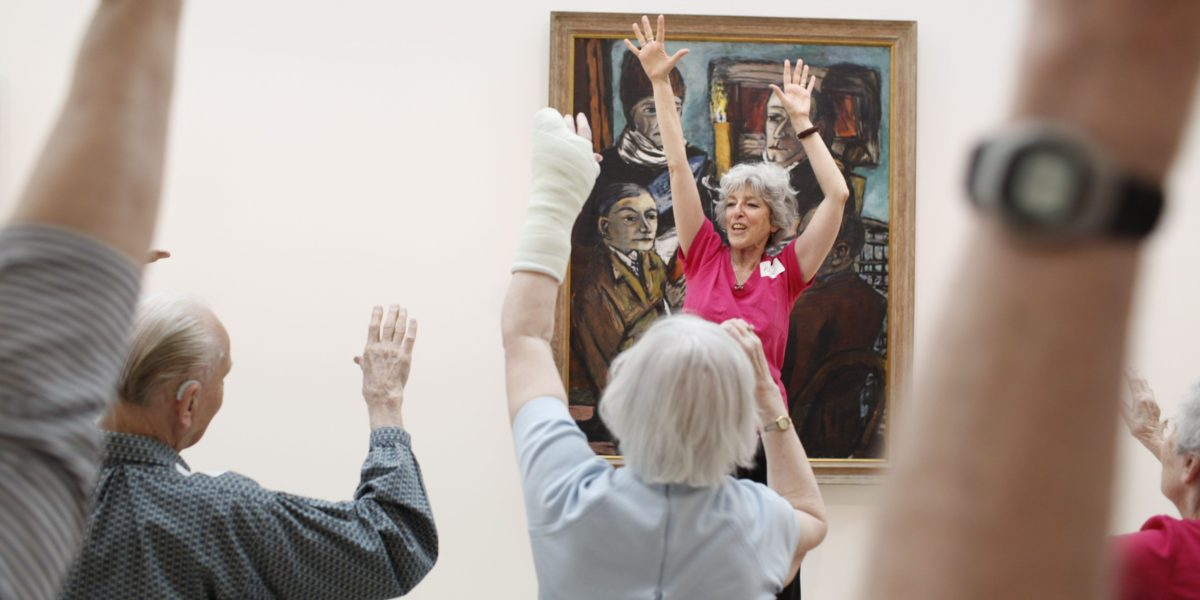 Alice Bloch leads Alzheimer's patients and caregivers through a series of light exercises during Kemper Art Reaches Everyone (KARE), a new program sponsored by WUSTL's Mildred Lane Kemper Art Museum in collaboration with Maturity and Its Muse. (Photo: Whitney Curtis/Washington University)