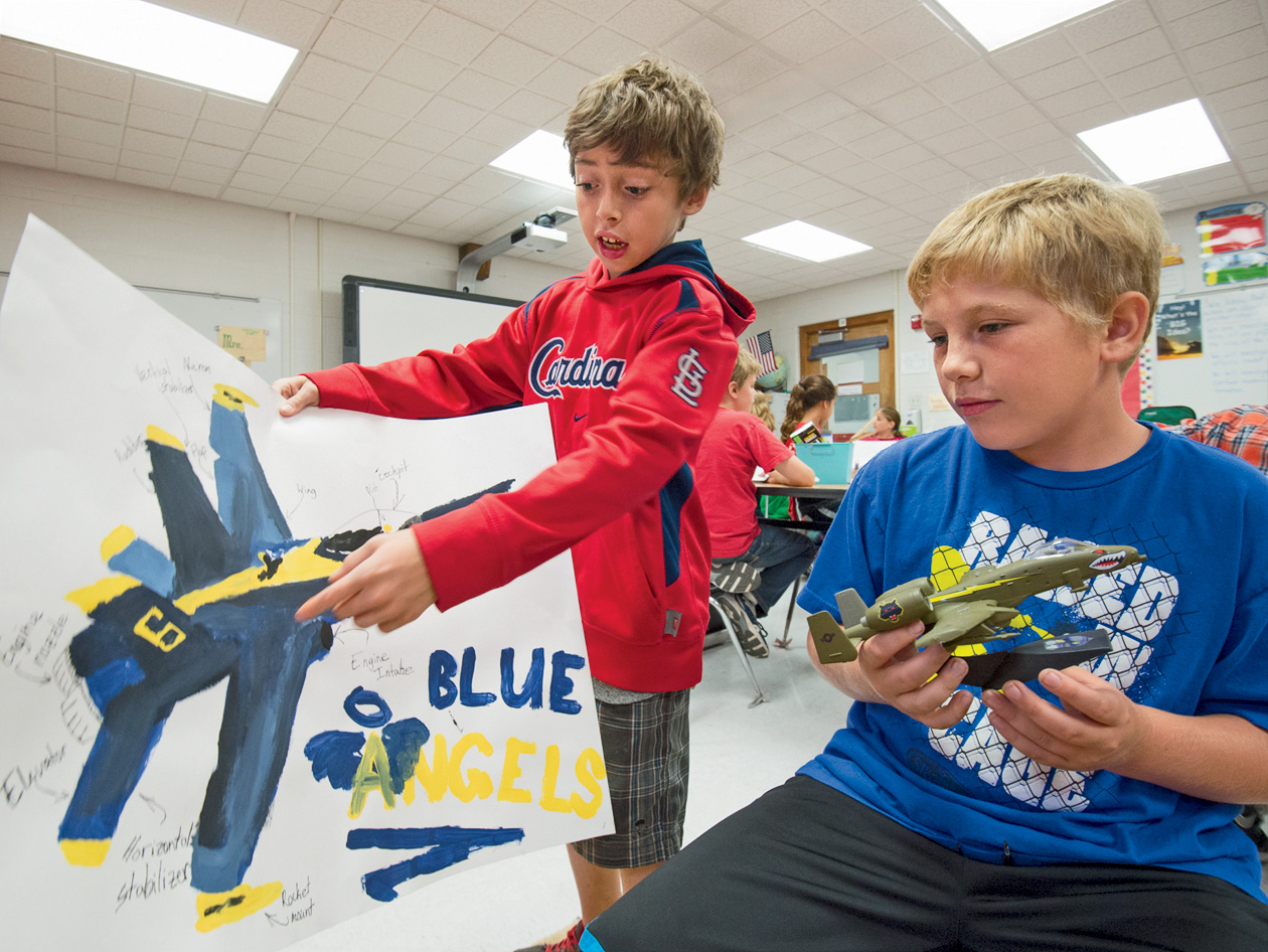 """Georgene Collier's 5th-grade class in the Hazelwood School District shows off their individual portfolio projects. Zach Gonzalez (left) and Dakota Fort chose aviation as their portfolio project. Zach, whose father is a pilot, drew a """"Blue Angels"""" F/A-18 Hornet and Dakota built an A-10 Warthog used mainly to hurt and destroy tanks and heavy machinery. (Photo: Joe Angeles)"""