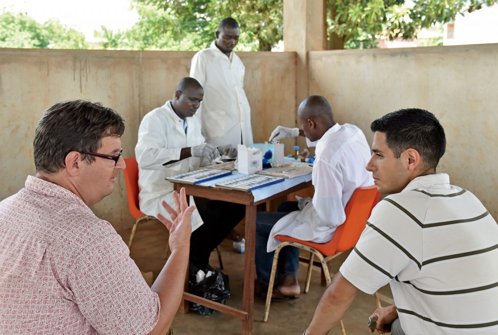 When Washington University researchers, such as Peter Fischer (lower left), PhD, associate professor of medicine, and Joshua Bogus (lower right), MPH, assist in-country partners (background) and cultivate ongoing collaborations, they create a more sustainable model for long-term global impact. (Photo: Issouf Sanogo/Agence France-Presse)