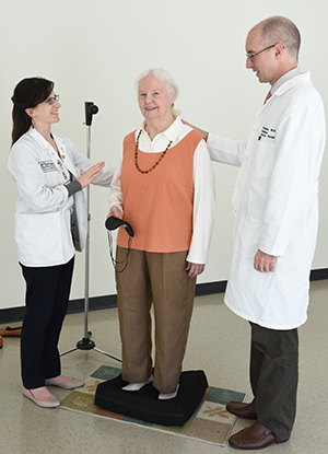 Timothy Hullar, MD, (right) and medical student Miranda Colletta help patient Audrey Miller prepare for a balance test. Older adults with hearing loss appeared to perform better on balance tests with both hearing aids on, according to Hullar's research.
