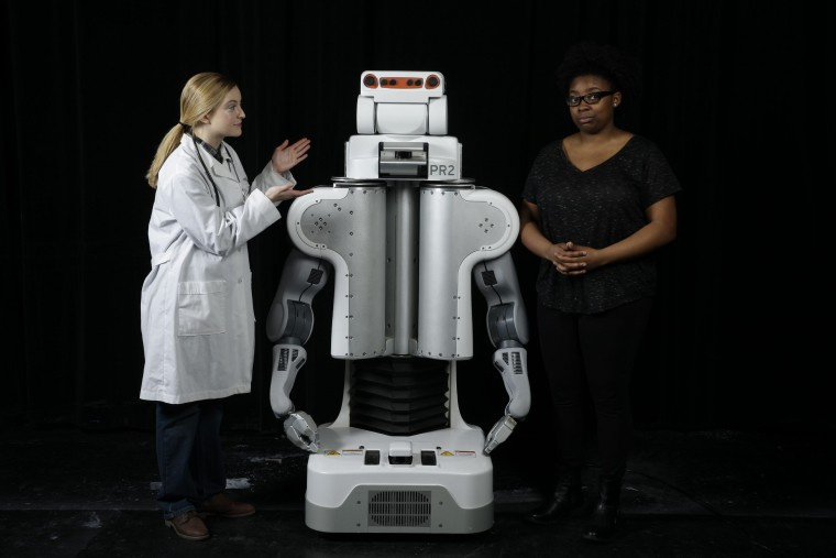 Doctor and patient standing next to robot.