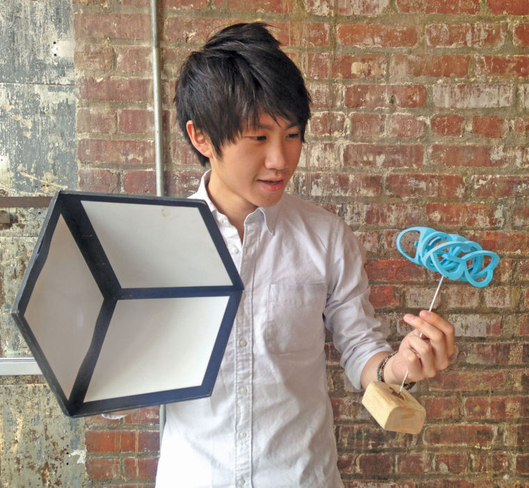 Justin Au holding two illusions for the OK Go video The Writing is on the Wall