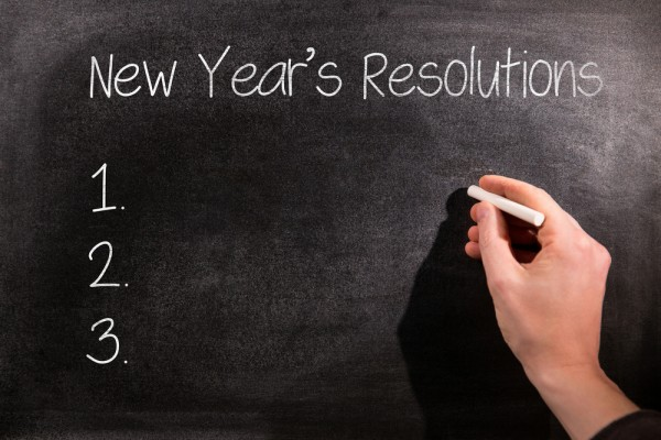 A hand writes new year's resolutions on a blackboard