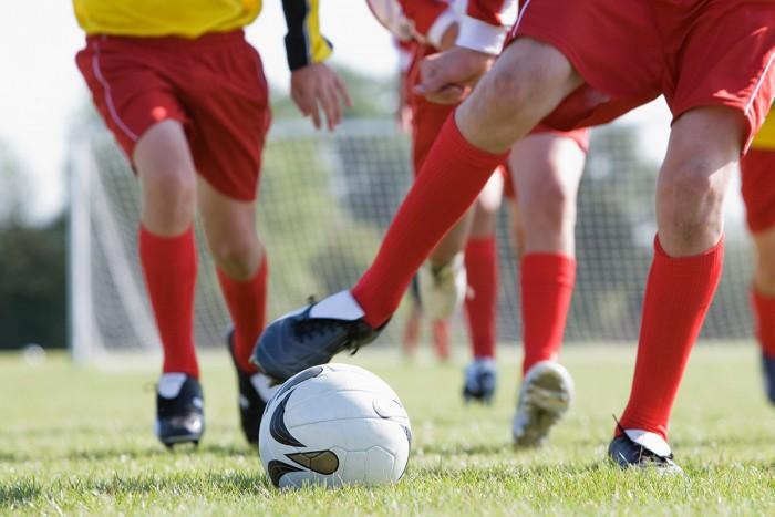 soccer players kicking a ball
