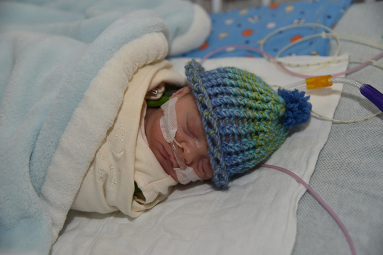 Preterm baby with knit hat.