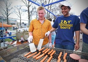 Carson Gaines, left, and Addy Shah prepare food at the Zeta Beta Tau food booth during 2014 Thurtene Carnival. (Photo: James Byard/Washington University)