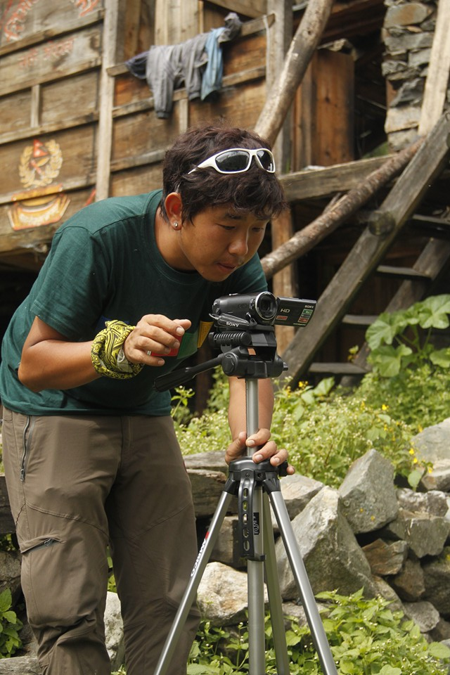 Nubri team member Nyima Samdrub preparing to video record an interview with an earthquake survivor.