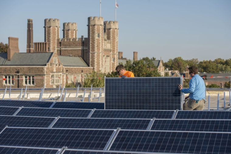 Workers installing solar panels on Hillman Hall.