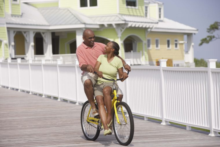 Older couple riding bicycle on boardwalk