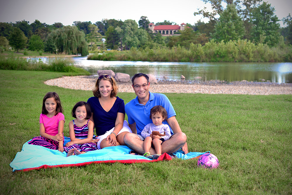 John Inazu relaxes in Forest Park last summer with his wife Caroline, and their children (from left) Lauren, 8, Hana, 6, and Sam, 3. (Photo: James Byard/Washington University)