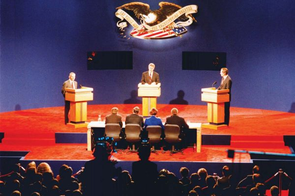 1992 presidential debate stage. Ross Perot, Bill Clinton and George HW Bush stand behind podiums on a red carpeted stage.