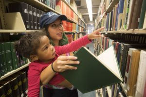 SATURDAY, SEPT. 24, 2016 - Washington University student Julia Zigman, with the Kappa Delta sorority, gives a tour of the library to Sophia Hill, 3, during Greek Day of Service, now an annual tradition, that hosts dozens of KIPP families on the Washington University campus. Young KIPPsters and their parents toured campus and participated in activities. The program gives young students a look at college life. Photo by Jerry Naunheim Jr./WUSTL Photos