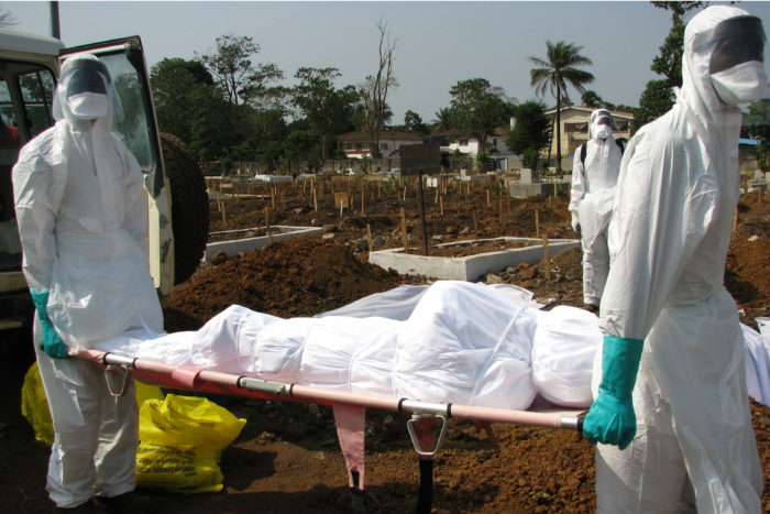 How the Ebola virus replicates and interacts with the body is the focus of a $13 million grant awarded to a team led by researchers at Washington University School of Medicine in St. Louis. These studies may lead to the development of treatments for the deadly disease. Above, during the Ebola outbreak from 2014 to 2016, workers in protective gear carry the body of an Ebola victim in a cemetery in Sierra Leone.