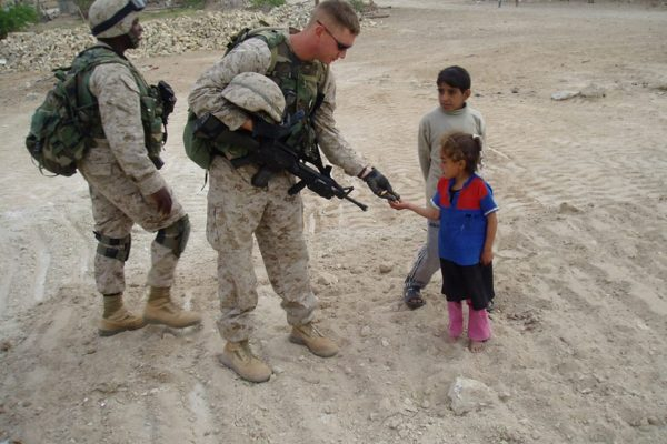 Petersen hands out Jolly Ranchers to Iraqi children in 2003.