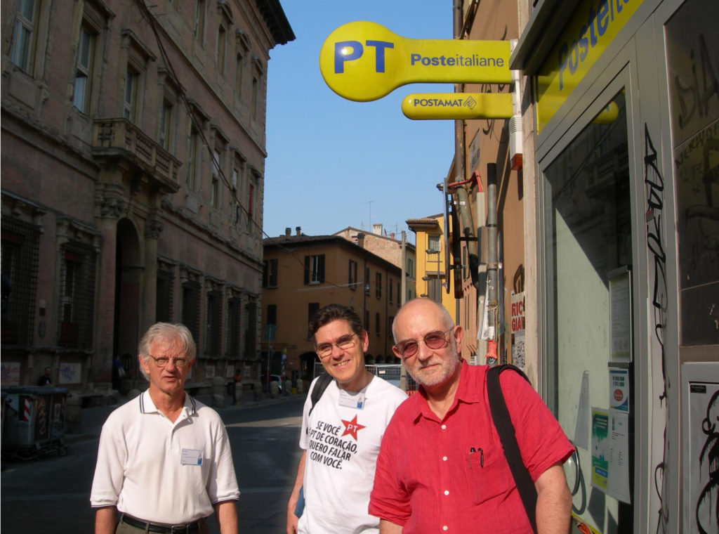 Bender with distinguished fellow physicists Barry McCoy (Stony Brook, left) and Sir Michael Berry (Bristol, right) in Italy looking for evidence that the universe is PT symmetric. The T-shirt reads in Portuguese, If PT is in your heart, I want to talk to you. Courtesy photo.