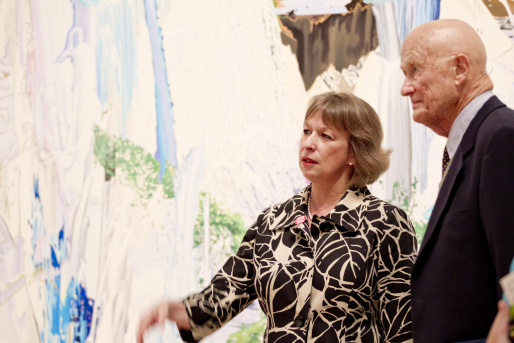 "James M. Kemper Jr, who died Dec. 15, discusses Corinne Wasmuht's ""Llanganuco Falls"" (2008) with Sabine Eckmann, the William T. Kemper Director and chief curator of the Mildred Lane Kemper Art Museum. ""I liked the Wasmuht because of the water play and the road,"" said Kemper, who helped the museum acquire the painting. ""As a visual work it is quite impressive and lighthearted—until you figure out what you're really looking at."" He also appreciated its historical significance, noting that ""older Germans were very skeptical of anything that had to do with outdoor life (or youth culture) because it was all associated with Hitler."" (Photo: Whitney Curtis/Mildred Lane Kemper Art Museum)"