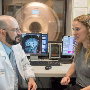 Bradley Schlaggar discusses a brain scan with a student