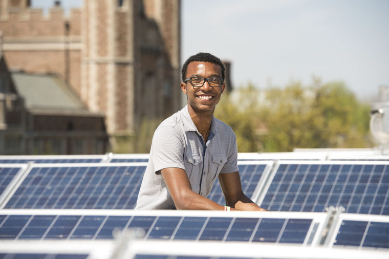 Deko Ricketts, BS '17, among the solar panels on the top of Hillman Hall.