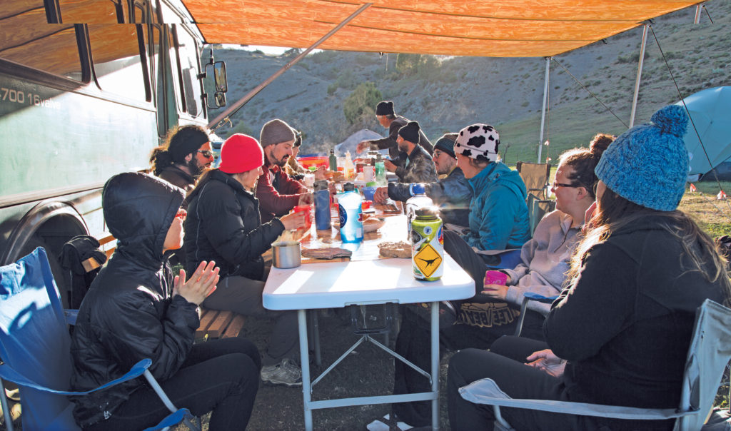 "Under a canopy hanging from the ­""Science Bus,"" researchers eat their meals and discuss excavation details. Their nearby tent camp (see pg. 27) allows the team to live in much the same way as the nomads who once populated the area. (Photo: Thomas Malkowicz)"