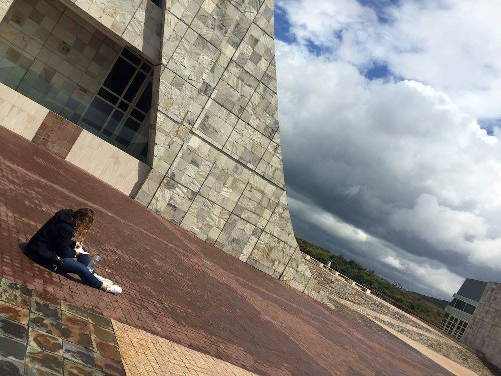 In a slanted photo, a girl sits on the floor next to a curved facade of a building, sketching in a book.