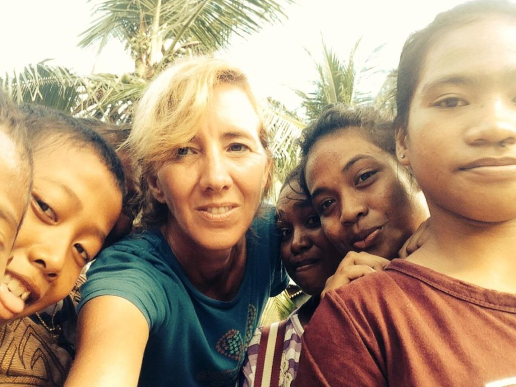 Robin McDowell takes a selfie with kids on the Indonesian island of Benjina, where hundreds of men were being forced to work against their will on Thai fishing trawlers. McDowell avoided the attention of officials for several days by hanging out with village children, practicing English with them. (Courtesy photo)