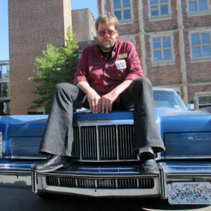 Gerry Rohde on hood of a car