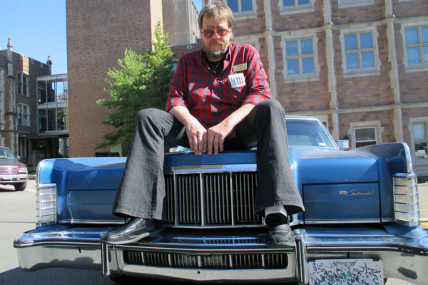 Gerry Rohde on hood of a car