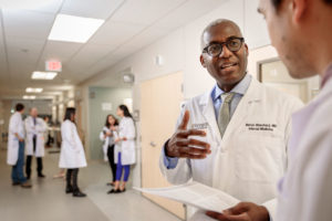 Melvin Blanchard, MD, talks with Andrew Young, MD, PhD, at the Center for Outpatient Health