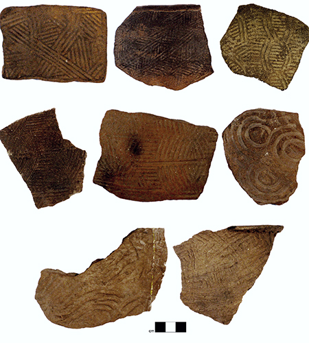 Examples of the kinds of pottery produced by people living across southern Appalachia between AD 800 and 1650. The unique symbols were stamped onto the pottery when the clay was still wet using carved wooden paddles. These designs, along with the varying characteristics of the specific kinds of clay used to produce the pottery, were used to reconstruct social networks among these communities. Photo credit: Jacob Lulewicz.