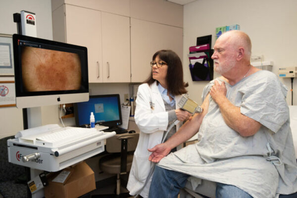 dermatologist conducts skin exam on patient