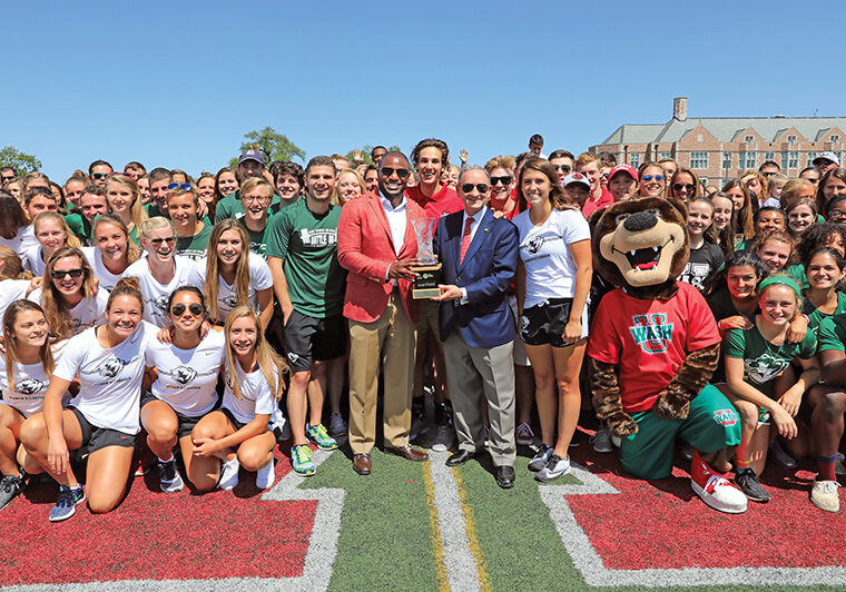 On Sept. 2, 2017, Anthony J. Azama, the John M. Schael Director of Athletics, and Chancellor Wrighton recognized all student-athletes from the previous year during halftime of a football game — an annual fall ritual. In turn, the athletes presented the chancellor with the trophy for WashU's second-place finish in the Division III Learfield Directors' Cup standings. (James Byard/WUSTL Photos)