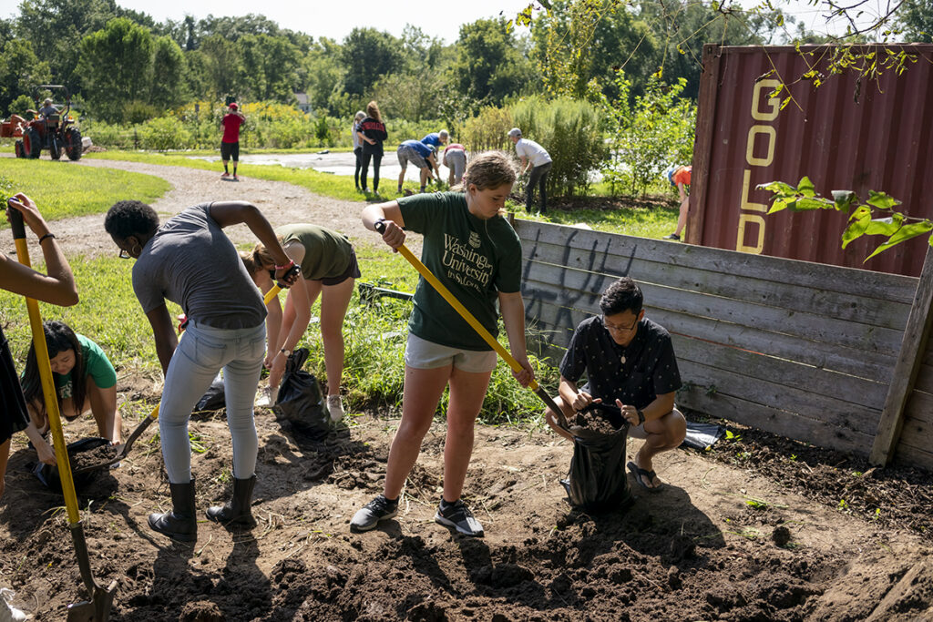 students shovel dirt in garden