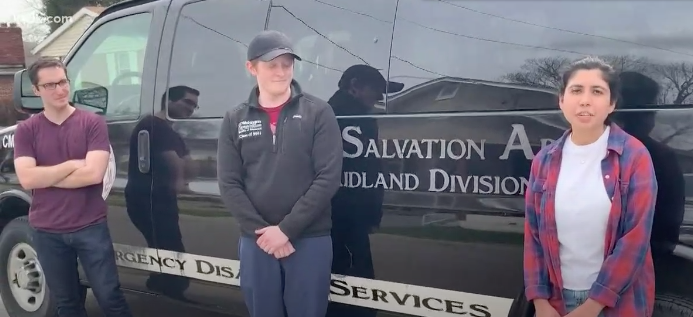 Three students stand in front of Salvation Army van