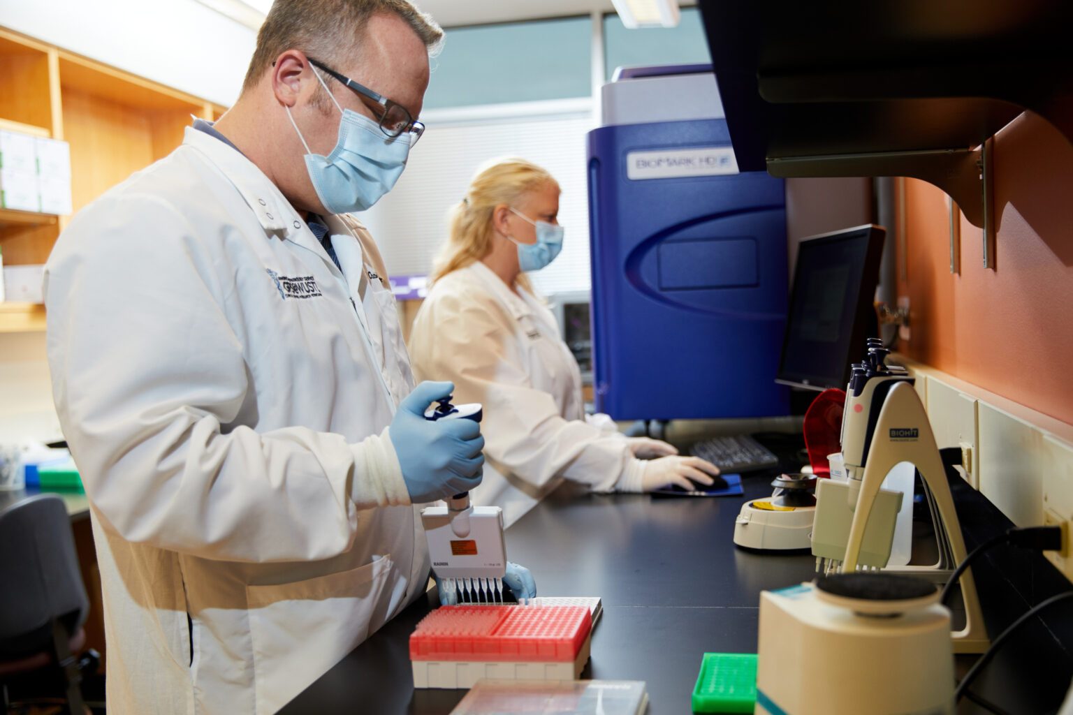 Washington University School of Medicine in St. Louis has developed a saliva-based test for COVID-19 that is faster and easier than the swab tests currently in use. Chris Sawyer, lab manager, and Lauren Burcea, clinical lab manager, work with test materials at the university's Genome Technology Access Center. (Photo: Matt Miller/School of Medicine)