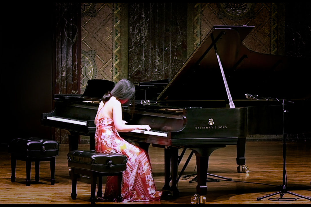 Young woman playing the piano at a recital